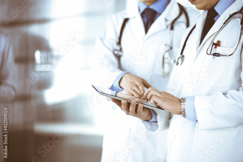 Group of unknown doctors use a computer tablet to check up some medical names records, while standing in a hospital office. Physicians ready to examine and help patients. Medical help, insurance in