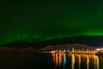 Zorza polarna przy wybrzeżu, latarnia morska. Ocen góry Norwegia skandowania