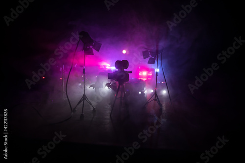 Fototapeta Action movie concept. Police cars and miniature movie set on dark toned background with fog. Police car chasing a car at night. Scene of crime accident. obraz