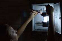 Power Outage In House. Extra Light Went Out In Room. A Person With A Lantern Checks Electrical Panel.