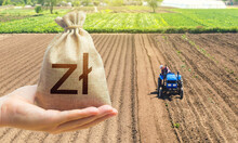Hand With A Polish Zloty Money Bag On The Background Of A Farm Field With A Tractor. Land Lease, Land Market. Investments In Agriculture And Agribusiness. Subsidies Support For Agricultural Producers.