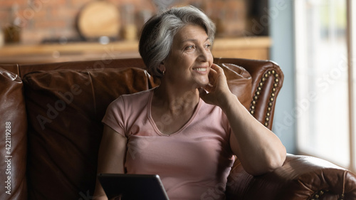 Nostalgia. Peaceful smiling elderly aged female grandma sit on comfy couch hold tablet dream distracted from gadget screen. Pensive older hispanic woman rest of pad computer lost in positive thoughts