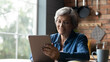 Free time with gadget. Positive elderly hispanic granny relax at home by window use tablet device contact children online chat in app read latest news. Happy mature woman surf internet on digital pad
