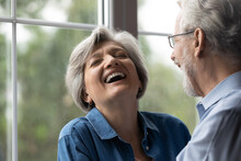 Close Up Shot Of Aged Family Couple Have Fun At Home Laugh Recalling Amusing Incident From Youth In Memory. Joyful Retired Husband Make Beloved Wife Cry With Laughter Cheer Her Up With Good Funny Joke