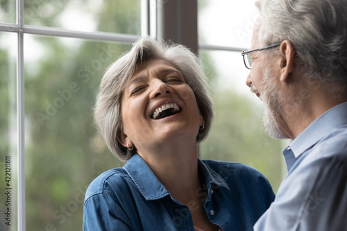 Fotografering Close up shot of aged family couple have fun at home laugh recalling amusing incident from youth in memory