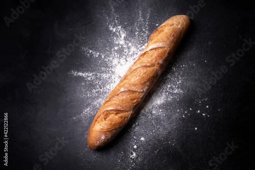 Obraz na plátně Crispy french baguette in splashes of wheat flour on a black background