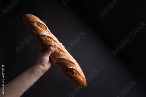 Fototapeta Female hand holding a crispy French baguette on a black background obraz