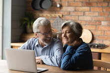 Old Age And Modern Tech. Retired Family Couple Sit At Kitchen Table Use Laptop Watch Photo Video Read Latest News Online. Aged Husband Share Discuss Interesting Information On Website With Senior Wife