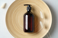 Dark Amber Glass Bottle And Dried Flowers On Plate. Natural Skincare SPA Beauty Product Design. Flat Lay, Top View.