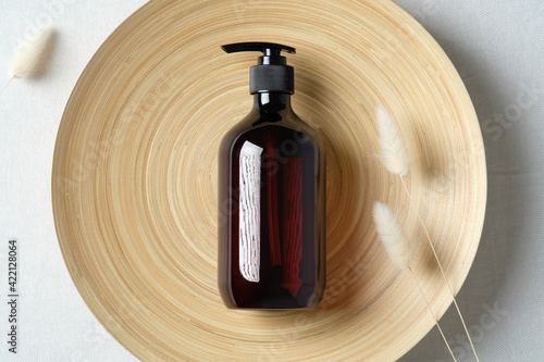 Fotografia Dark amber glass bottle and dried flowers on plate