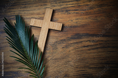 Palm sunday background. Cross and palm on wooden background.