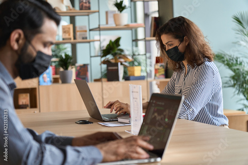 Obraz Young latin woman wearing face mask working on laptop keeping safe distance. Diverse people in facemasks using computers sitting at table in office coworking or cafe keeping safe social distance. - fototapety do salonu