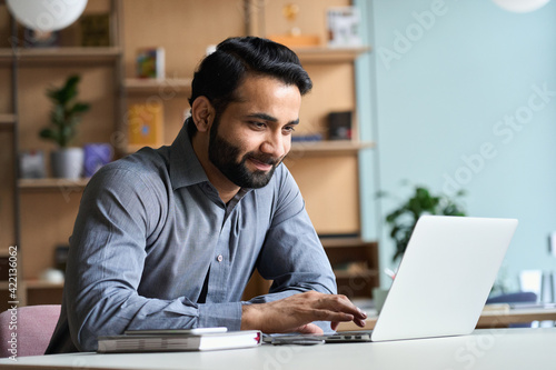 Fototapeta Smiling indian business man working on laptop at home office