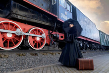 A Beautiful Girl In A Historical Retro Dress Against The Background Of An Old Steam Locomotive At The Station.