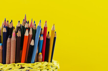 Many Colored Pencils Standing Upright In A Basket Of Paper On A Yellow Background