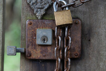 Three Oxidized Locks On An Old Wooden Gate With Slime: Latch, Doorknob And Chain With Padlock.
