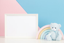 White Blank Frame With Teddy Bear And Pastel Toy Rainbow On White Desk. Baby Room Art Frame Mock Up With Baby Kid Toys Over Pink And Blue Background