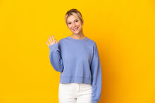 Young Russian Woman Isolated On Yellow Background Saluting With Hand With Happy Expression