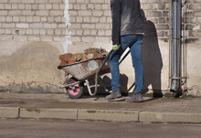A Worker Carries Bricks In A Brick Cart In The City.