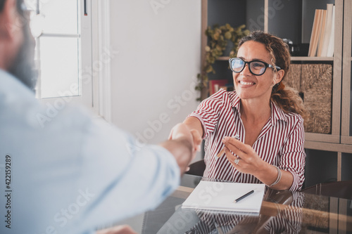 Smiling caucasian female hr manager handshake hire male candidate at job interview make good first impression, happy mixed race client shake hand of bank broker, respect, business agreement concept