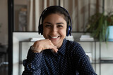 Screen view portrait of smiling young Indian female employee in earphones have webcam digital virtual event in office. Headshot of happy ethnic woman worker in headphones talk speak on video call.