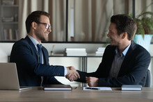 Smiling Businessmen Shake Hands Close Deal Make Agreement At Meeting In Office. Happy Male Colleagues Or Business Partners Handshake Get Acquainted Greeting At Briefing. Teamwork, Partnership Concept.