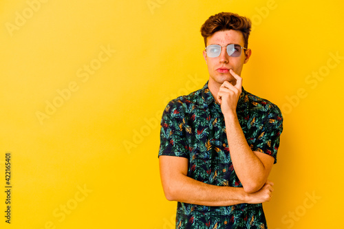 Young caucasian man wearing a Hawaiian shirt isolated on yellow background looking sideways with doubtful and skeptical expression.