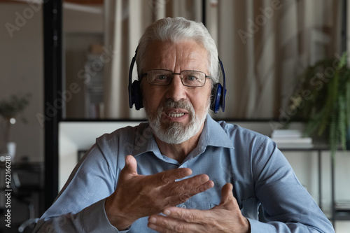 Headshot portrait screen view of middle-aged Caucasian male employee in headphones talk speak on video call in office. Senior businessman have webcam digital conference online. Virtual event concept.