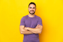 Young Caucasian Handsome Man Isolated On Yellow Background Keeping The Arms Crossed In Frontal Position