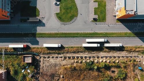 Fotografiet Large long truck drives along empty modern road past contemporary huge storehous