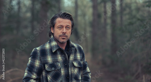 Fotografia Blonde man in checkered coat standing in the woods.