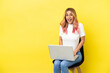 Young woman sitting on a chair with laptop over isolated yellow background with surprise facial expression