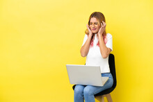Young Woman Sitting On A Chair With Laptop Over Isolated Yellow Background Frustrated And Covering Ears