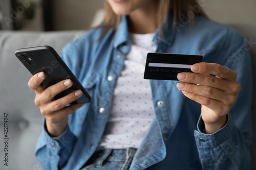 Obraz na plátně Close up woman holding plastic card and using phone at home, young female making