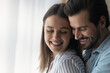Leinwandbild Motiv Close up smiling woman and man, young couple enjoying tender moment, hugging, standing at home, happy wife and husband expressing love and care, spending free time together, romantic date concept