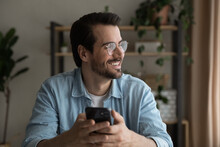 Close Up Smiling Dreamy Man Wearing Glasses Distracted From Phone, Looking To Aside, Holding Smartphone, Visualizing Good Future, Waiting For Call Or Message, Enjoying Leisure Time With Gadget