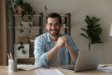 Head Shot Portrait Smiling Confident Businessman Wearing Glasses Sitting At Table With Laptop And Documents, Looking At Camera, Successful Happy Entrepreneur Or Student Posing At Workplace