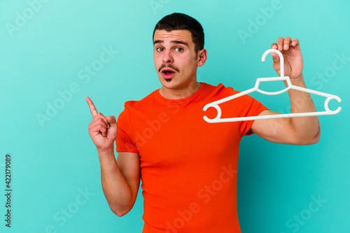 Fototapeta Young caucasian man holding a hanger isolated on blue background pointing to the