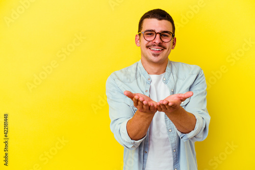 Young caucasian cool man isolated on yellow background folding lips and holding palms to send air kiss.