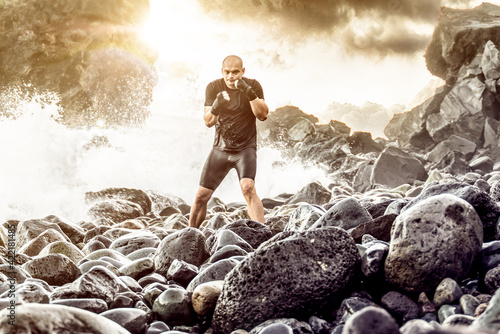 Tela Man exercising outdoor on the rocky ocean coast.