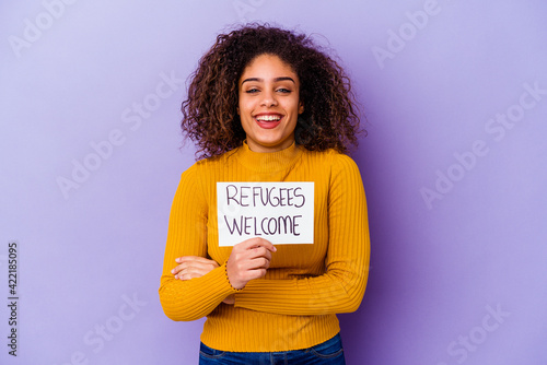 Photo Young African American woman holding a Refugees welcome placard isolated laughing and having fun