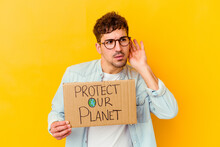 Young Caucasian Man Holding A Protect Our Planet Placard Isolated Trying To Listening A Gossip.