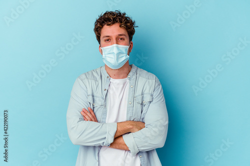 Fotografia, Obraz Young caucasian man wearing an antiviral mask isolated on blue background who feels confident, crossing arms with determination
