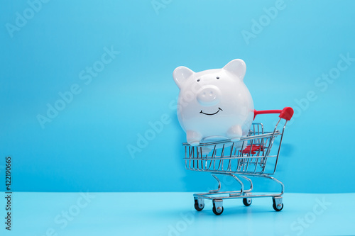 White piggy bank and shopping cart on blue background Fototapet