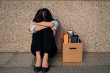 Unrecognized Young Woman Hiding Her Face After Being Laid Off From Job Due To Economic Recession Sitting With Carton Of Belongings On Floor And Crying