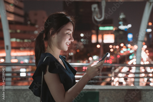 Fototapeta Side-view of beautiful young Asian happy woman standing over footbridge checking