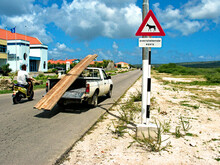 A Road Sign, A Pickup Car And A Scooter On A Road In Bonaire, Dutch Antilles; The Sign Informs Of Feral Donkeys Frequently Crossing The Road (English: 'beware Of Donkeys').