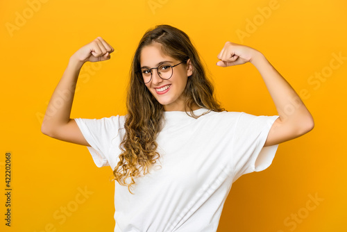 Fototapeta Young caucasian woman showing strength gesture with arms, symbol of power obraz