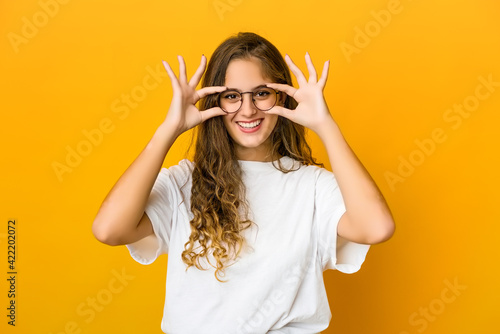Young caucasian woman showing okay sign over eyes