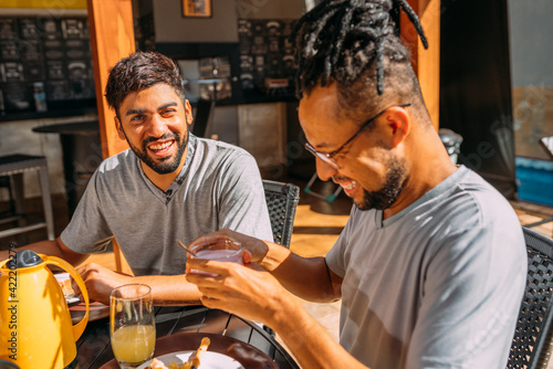 Fototapeta Happy latinx gay couple having coffee at home, on a sunny day obraz